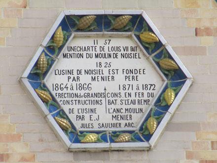 Historique du moulin de Noisiel encadré de cabosses en relief