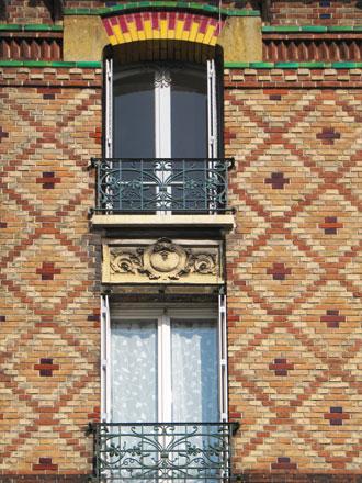 31 rue Rouget de l'Isle, décor très travaillé, plusieurs couleurs de briques et d'émaillage, briques en saillie, panneau en relief en allège