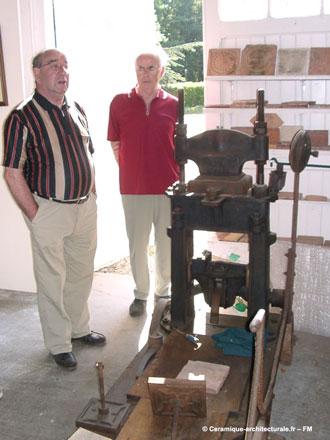 Michel Pasquier, à gauche devant une presse à carreaux, faisant visiter son musée privé – ph.2006