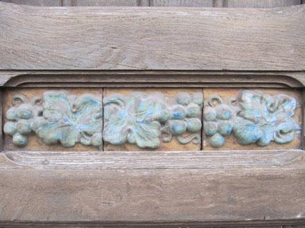 Frise de feuilles et grappes incluses dans la porte en bois, en grès de Gentil & Bourdet